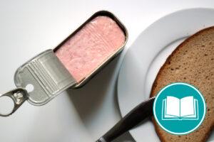 Geöffnetes Dosenfleisch, daneben ein Teller mit einer Scheibe Brot