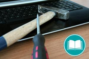 Hammer und Schraubendreher liegen auf einem Laptop, um die Einstellungen zu verändern.
