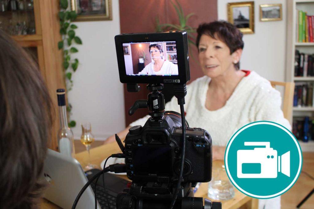 Frau wird am Kaffeetisch mit einer Kamera gefilmt