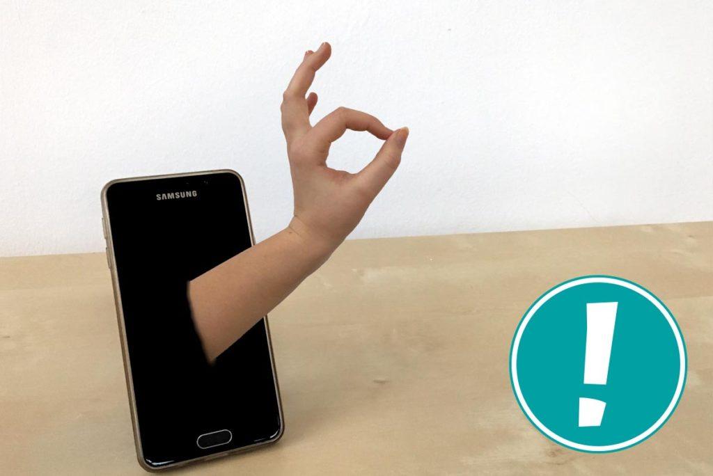 Eine Hand, die aus dem Handy kommt und ein OK Zeichen gibt