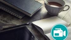 Kaffeetasse und ein aufgeschlagenes Notizbuch