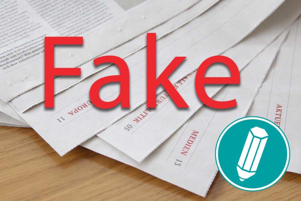 Zeitungen liegen auf einem Tisch und in dicker roter Schrift steht das Wort Fake darauf.