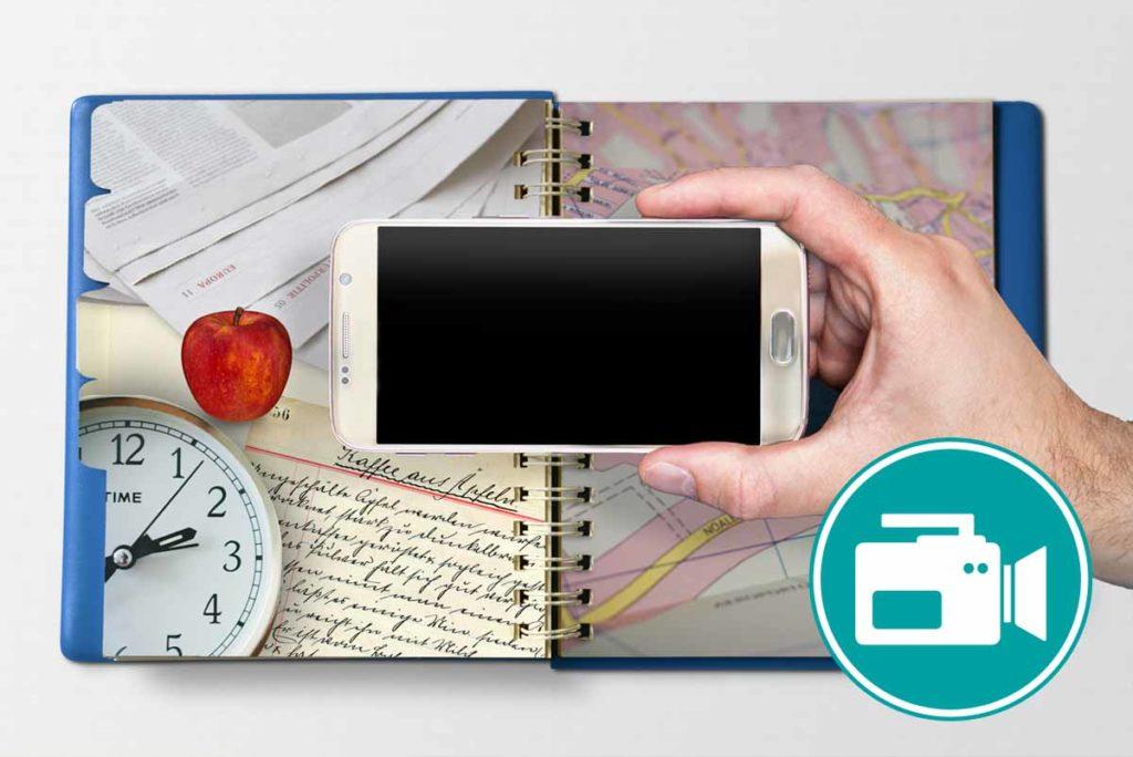 Ein SMartphone ist zu sehen. Im Hintergrund einUhr, eine Landkarte und Zeitungen.