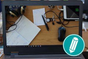 Auf dem Bildschirm eines Laptops ist ein unaufgeräumter Schreibtisch zu sehen.