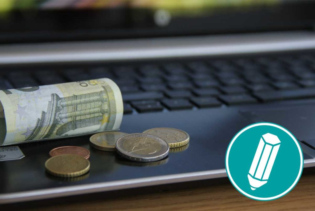 Auf einem Laptop liegt Geld.