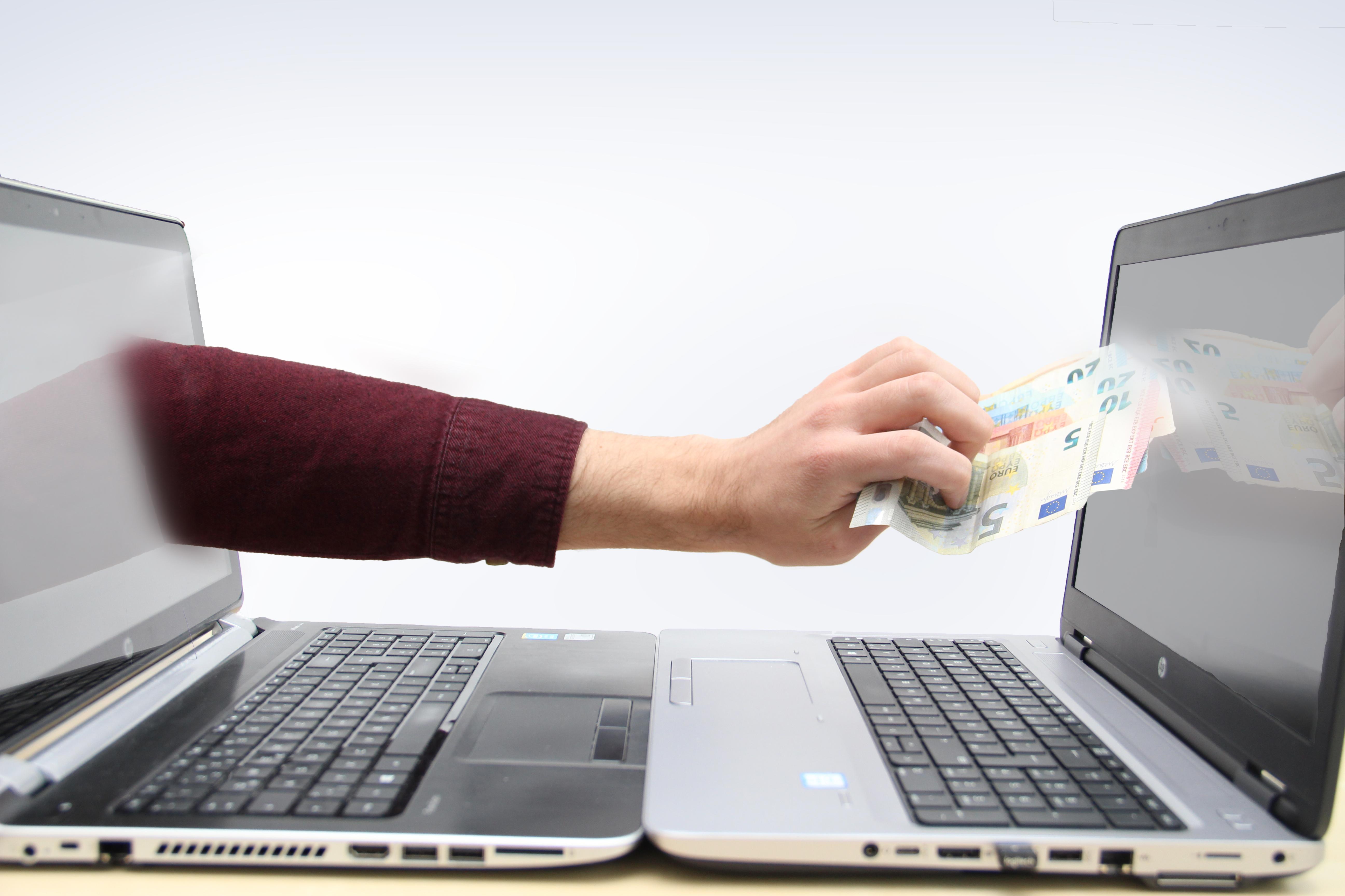 Eine Hand klaut Geld aus einem Laptop.