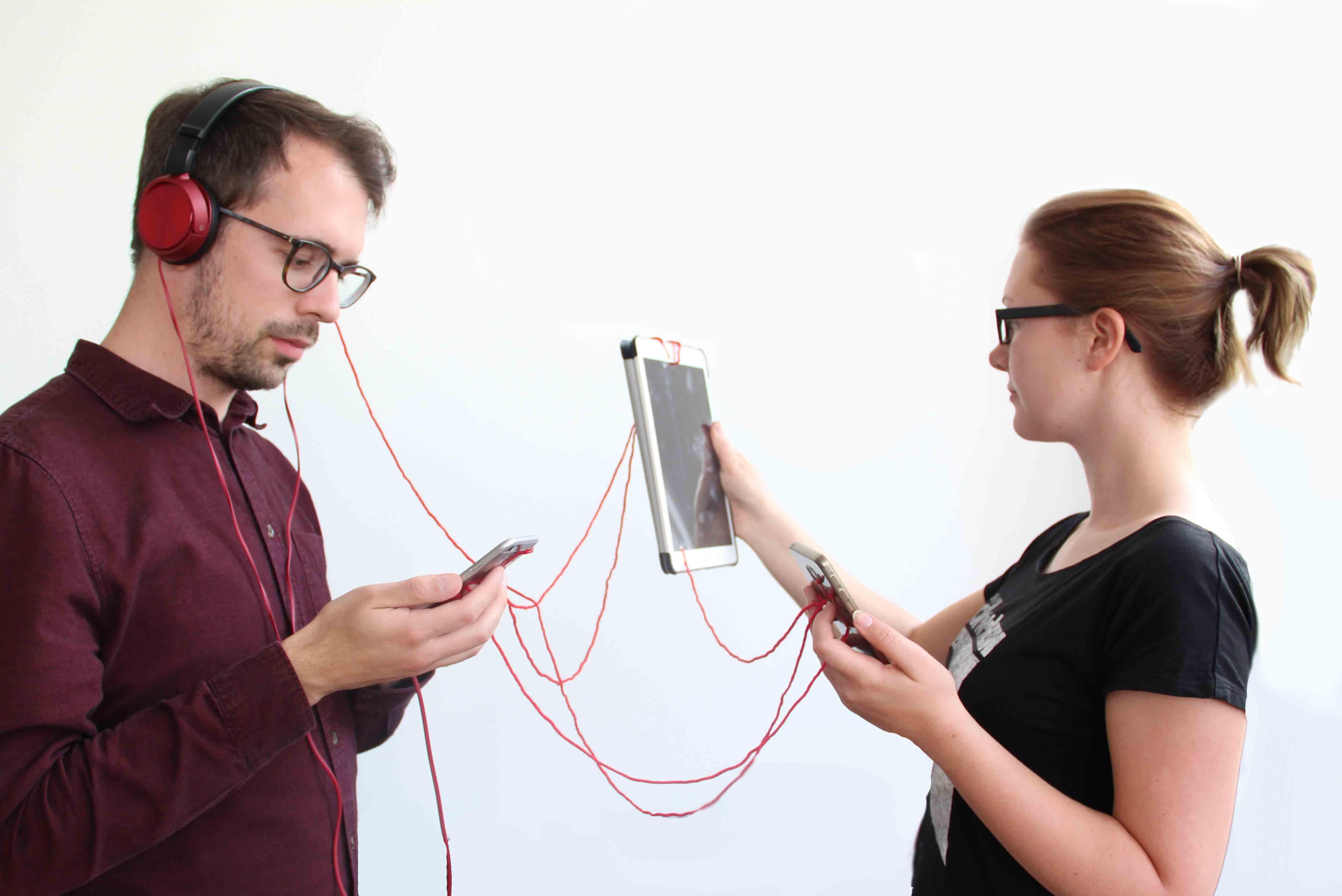 Zwei Menschen sind mit mehreren Geräten mit einem roten Faden verbunden.