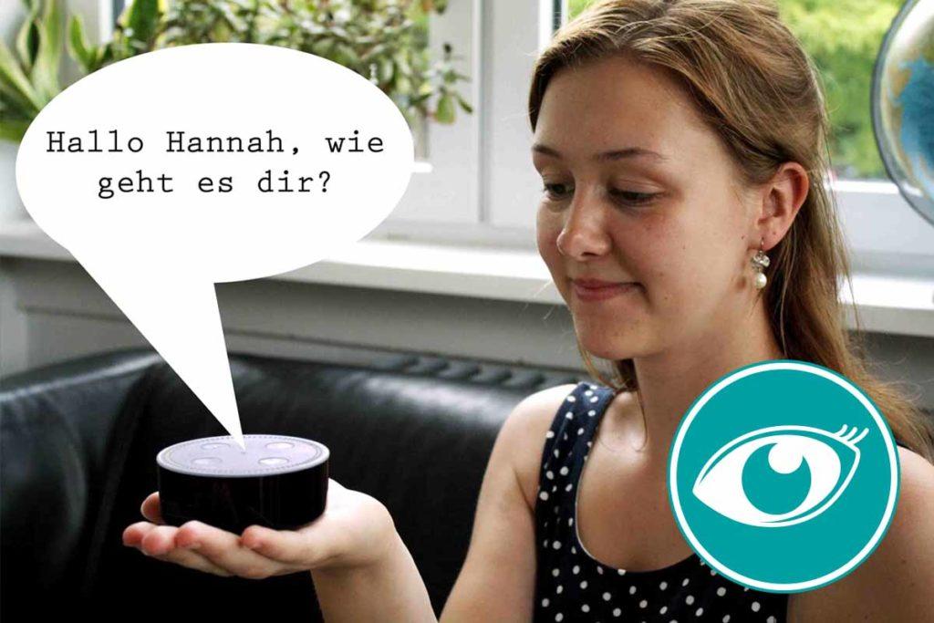 Eine Frau hält ein Sprachassistenz-Gerät in der Hand. Das Gerät grüßt sie.