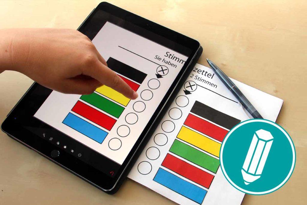 Man sieht einen Wahlzettel, sowohl auf einem Tablet, als auch auf Papier.