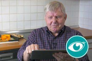 Ein Mann sitzt in der Küche und bestellt auf dem Tablet Lebensmittel.