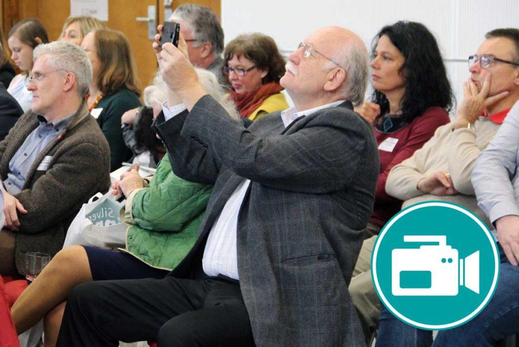 Ein älterer Mann macht mit seinem Smartphone ein Bild.