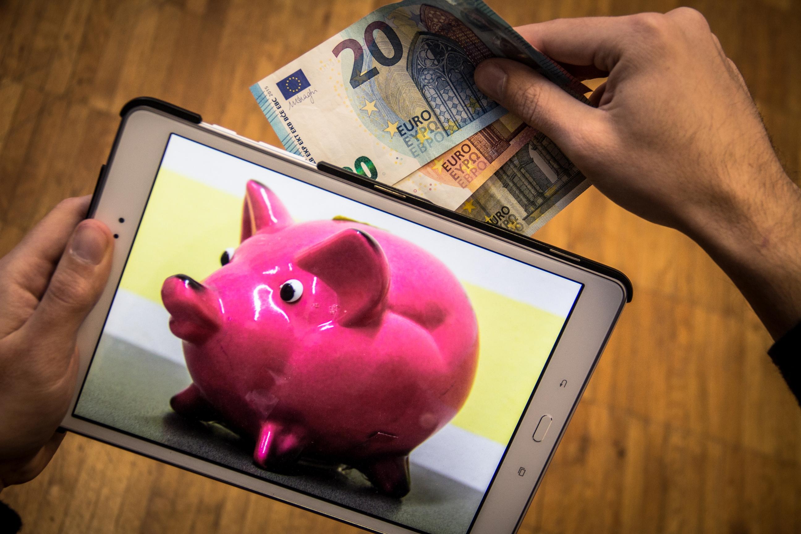 Auf einem Tablet ist ein Sparschwein abgebildet. Eine Hand steckt Geldscheine in das Sparschwein.