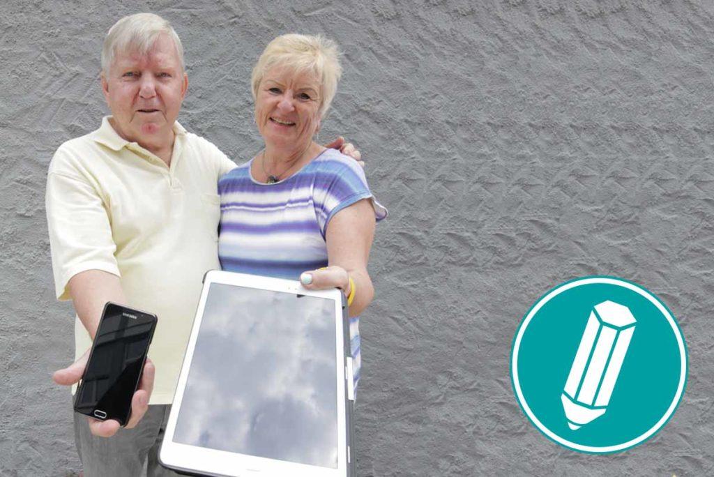 Ein älteres Pärchen hält ein Smartphone und ein Tablet in die Kamera.