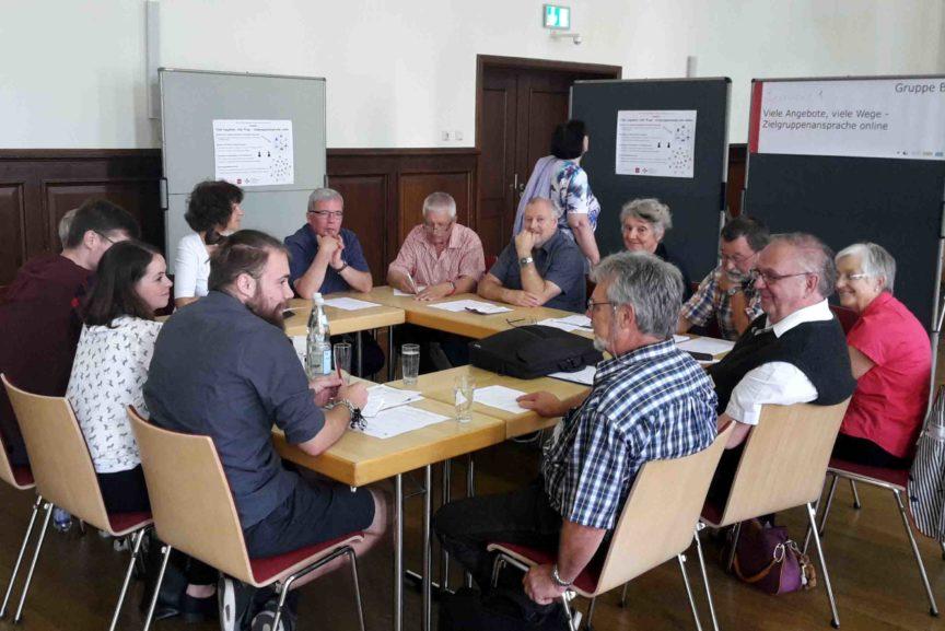 Eine Gruppe von Menschen sitzt gemeinsam an einem Tisch.