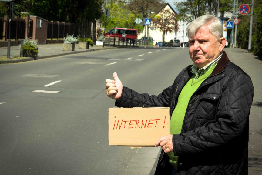 """Ein älterer Mann steht an der Straße und hält ein Schild hoch, auf dem """"Internet"""" steht."""