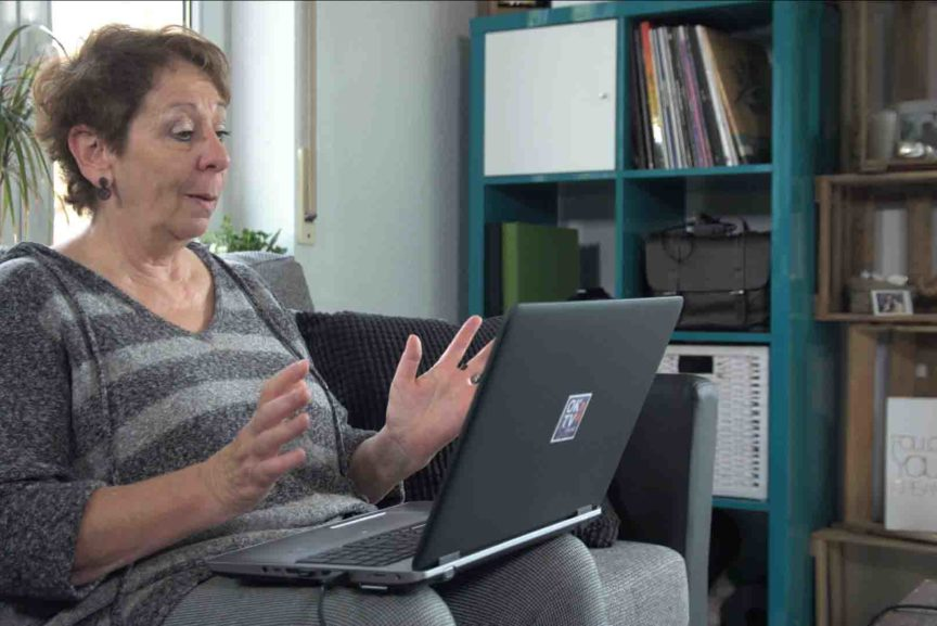 Eine ältere Frau sitz vor ihrem Laptop und ist überrascht.