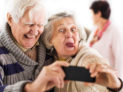 Cheerful senior couple making faces and having fun while taking a selfie with smart phone.