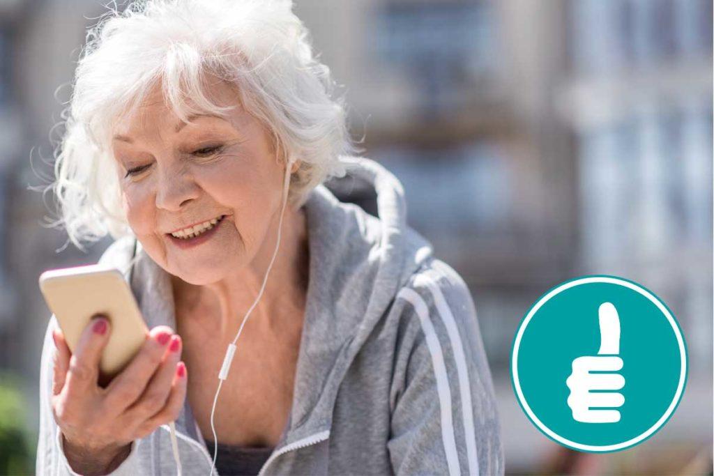 Eine älter Dame mit einem Smartphone in der Hand und Kopfhörern im Ohr.