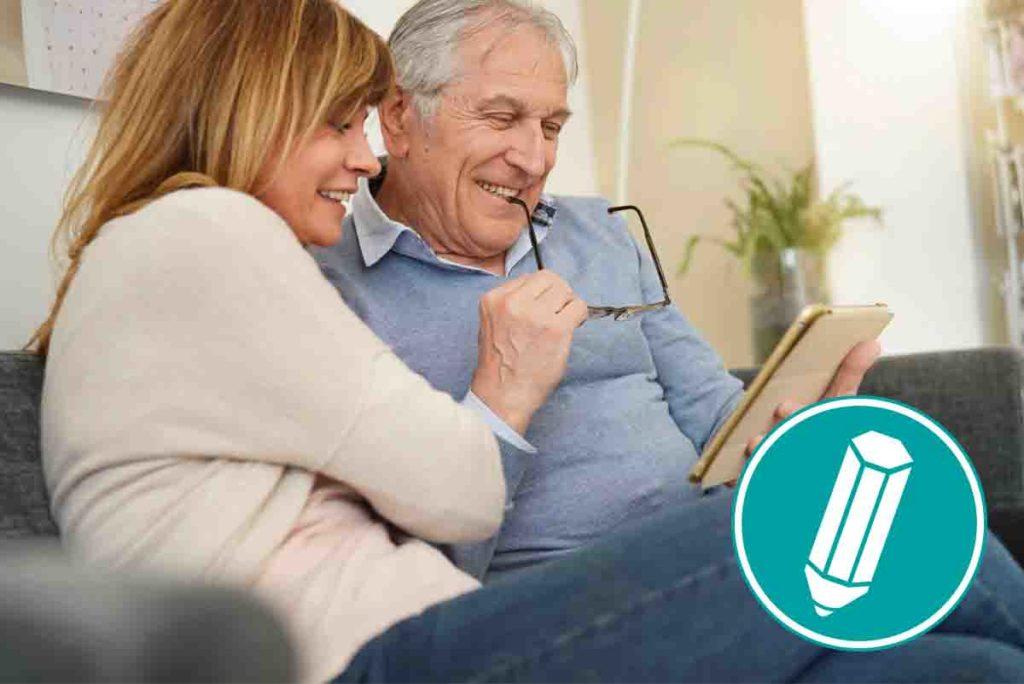 Älteres Ehepaar lacht und blickt auf ein Tablet