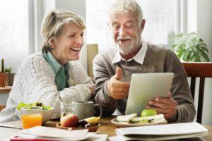 Zwei Menschen sitzen am Tisch und schauen sich etwas am Tablet an.