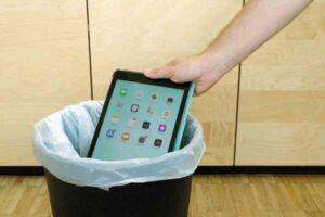 Jemand wirft ein Tablet in den Mülleimer