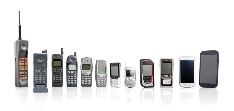 Man sieht die Entwicklung vom Handy zum Smartphone mit verschiedenen Handymodellen aus verschiedenen Generationen.