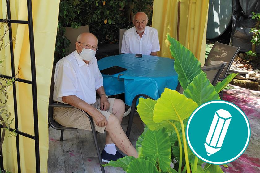Zwei Senioren sitzen im unter einem Pavillon und schauen auf ihr Smartphone und Tablet.