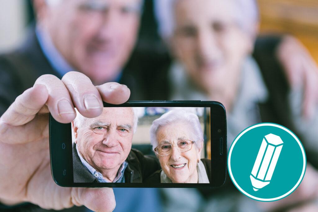 Zwei ältere Menschen machen mit dem Smartphone ein Selfie, fotografieren sich also selbst.