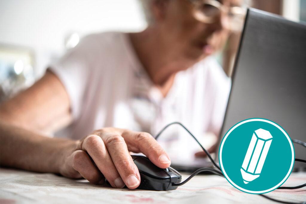 Eine ältere Frau sitzt vorm Laptop und klickt mit der Maus.