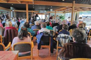 Der Raum ist gefüllt mit über 80 Personen. Die Menschen schauen nach vorne, wo die DigiBos sich vorstellen.
