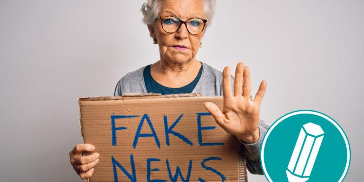 Ältere Frau hält ein Schild hoch auf dem steht: Fake News