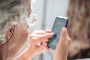 Eine ältere Frau tippt auf ihr Smartphone.