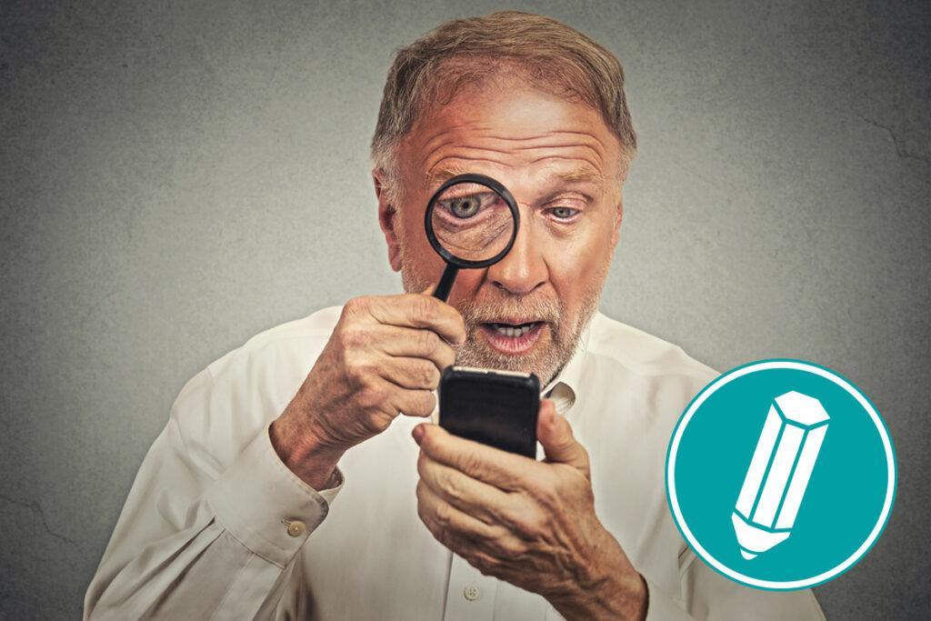 Mann schaut durch Lupe auf sein Smartphone.