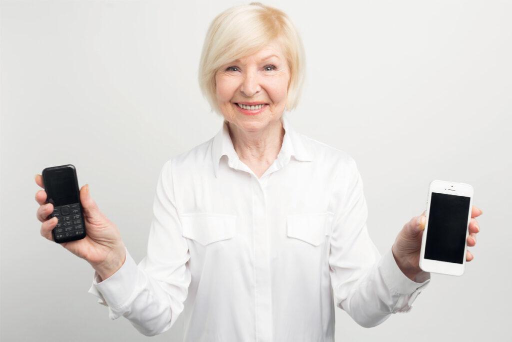 Ältere Frau hält zwei Smartphones in der linken und rechten Hand.