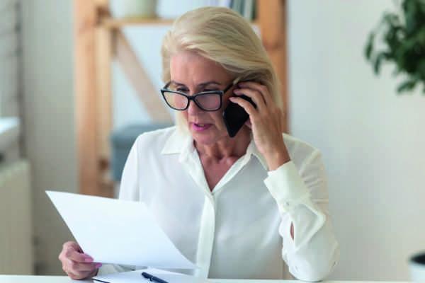Frau mit schaut auf Vertrag und telefoniert
